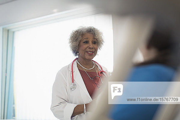Female senior doctor making rounds  talking with patient in hospital room