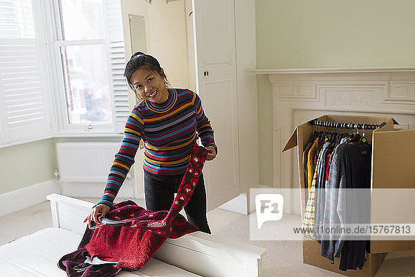 Portrait woman unpacking clothing from moving box in bedroom