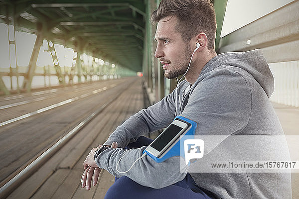 Young male runner resting  listening to music with headphones and mp3 player on train station platform