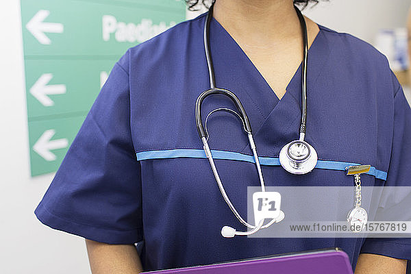 Close up female doctor wearing scrubs and stethoscope in hospital