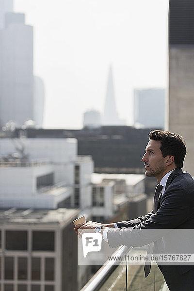 Nachdenklicher Geschäftsmann auf sonnigem  städtischem Balkon