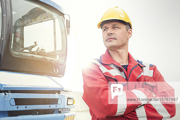 Confident dock worker standing outside truck at shipyard