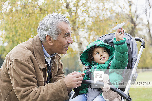 Grandfather with curious grandson in stroller