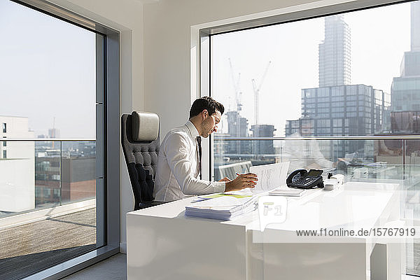 Businessman reviewing paperwork in sunny  modern  urban office