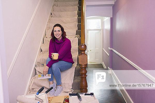 Portrait confident woman redecorating  looking at paint swatch on stairs Portrait confident woman redecorating, looking at paint swatch on stairs