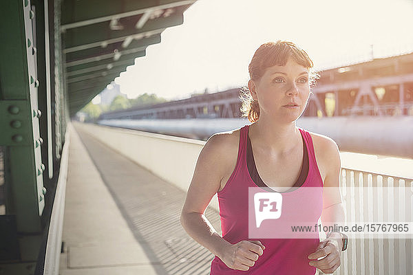 Determined young woman running along sunny train station platform