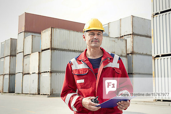 Portrait confident dock worker with clipboard and walkie-talkie at shipyard