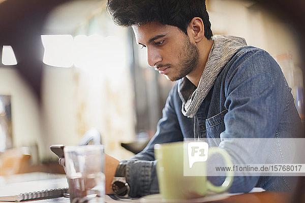 Fokussierter männlicher Student  der ein Smartphone benutzt