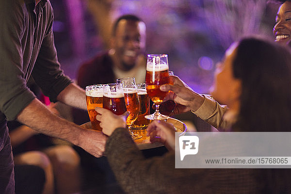 Man serving beer glasses to friends at party