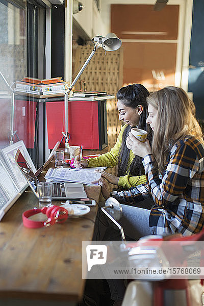 Young female college students studying in cafe window