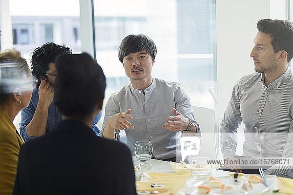 Geschäftsleute treffen sich  essen Sushi zu Mittag im Büro