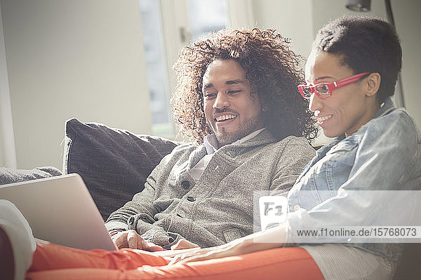 Couple relaxing  using laptop on sofa