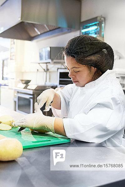 Konzentrierte junge Frau mit Down-Syndrom kocht in der Küche eines Cafés