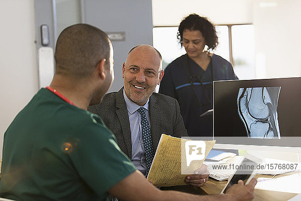 Doctor and nurse discussing digital x-ray at computer in clinic