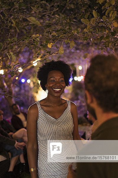 Happy young woman talking with man at garden party