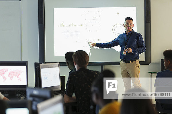 Male junior high teacher leading lesson at projection screen in classroom