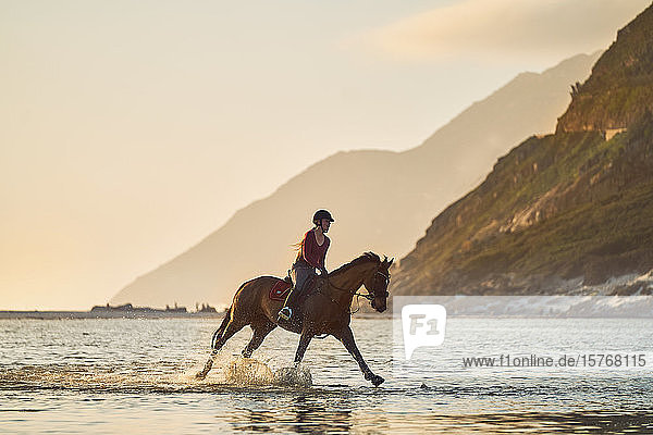 Young woman galloping on horseback in tranquil ocean surf