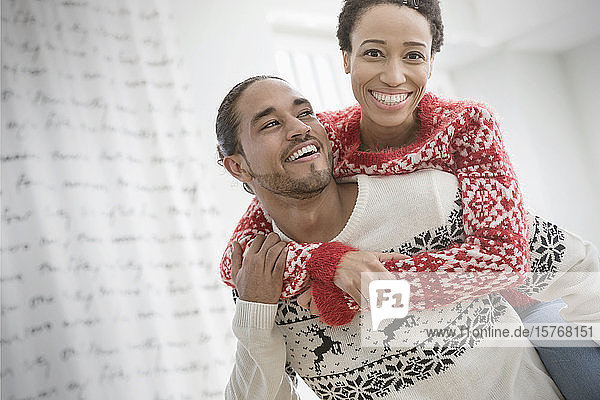 Portrait happy  playful couple in Christmas sweaters piggybacking