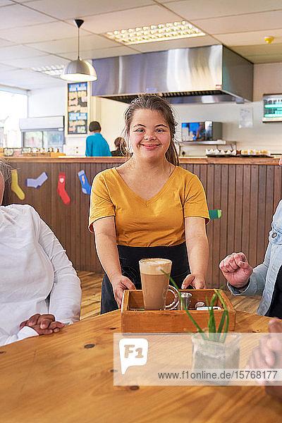 Porträt einer glücklichen jungen Kellnerin mit Down-Syndrom bei der Arbeit in einem Café