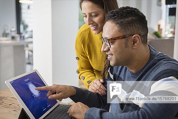 Ehepaar benutzt digitales Tablet und meldet sich mit Fingerabdruck an
