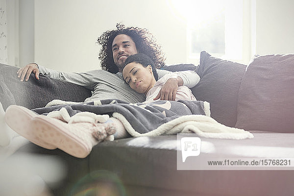 Affectionate couple relaxing  watching TV on sofa
