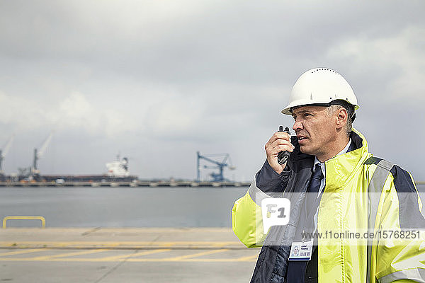 Dock manager with walkie-talkie at shipyard