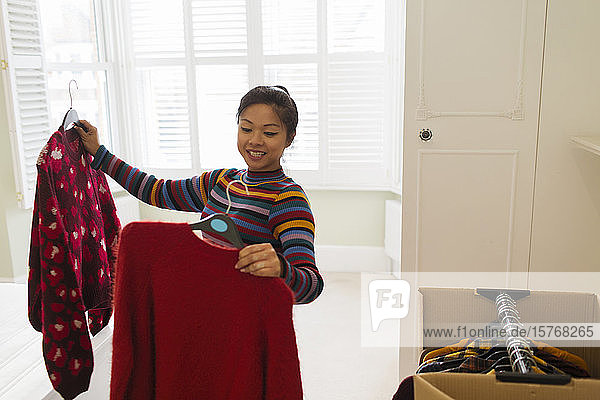 Smiling woman unpacking clothing from moving box in bedroom