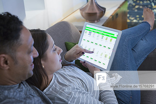 Affectionate couple relaxing  ordering groceries from digital tablet on living room sofa