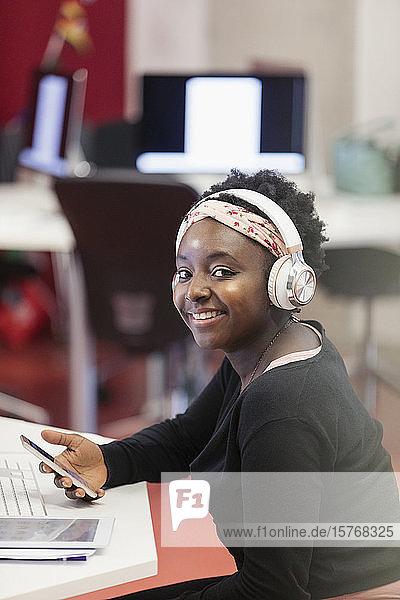 Portrait confident female student with headphones and smart phone Portrait confident female student with headphones and smart phone