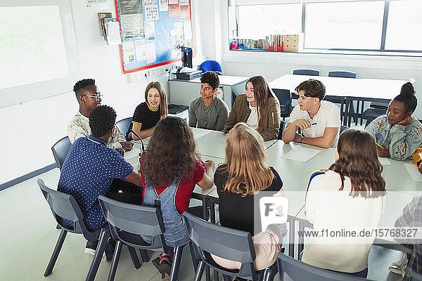 Gymnasiasten unterhalten sich im Debattierkurs am Tisch im Klassenzimmer