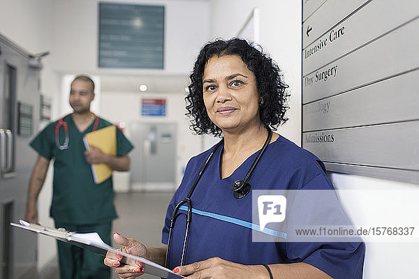 Portrait confident female doctor with medical chart  making rounds in hospital corridor Portrait confident female doctor with medical chart, making rounds in hospital corridor