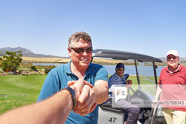 Personal perspective male golfers handshaking on sunny golf course Personal perspective male golfers handshaking on sunny golf course