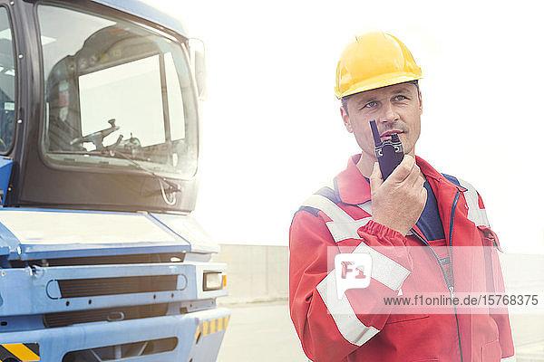 Dock worker using walkie-talkie outside truck at shipyard