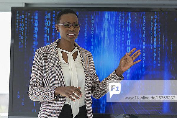 Geschäftsfrau  die eine Besprechung vor einem Fernsehbildschirm leitet