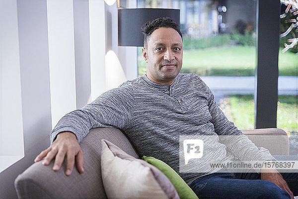 Portrait confident man on living room sofa Portrait confident man on living room sofa