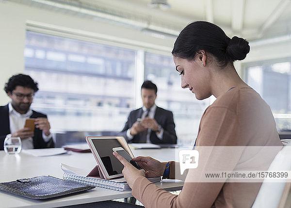 Geschäftsfrau benutzt Smartphone in Konferenzraumbesprechung