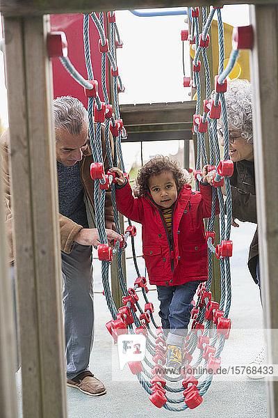 Grandparents playing with grandson at playground