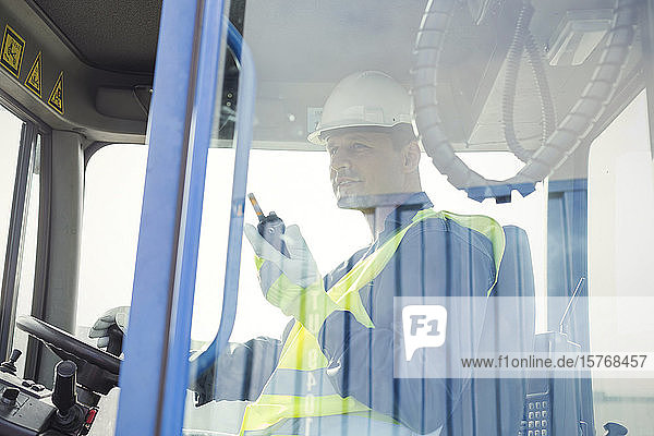 Dock worker with walkie-talkie operating forklift
