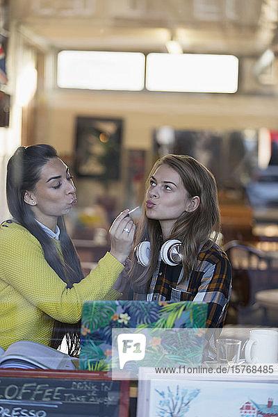 Junge Frauen tragen Lipgloss im Schaufenster eines Cafés auf