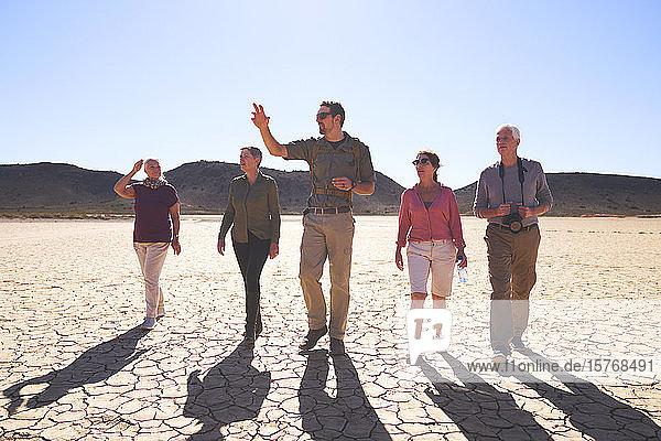 Safari tour guide leading group in sunny arid desert South Africa Safari tour guide leading group in sunny arid desert South Africa