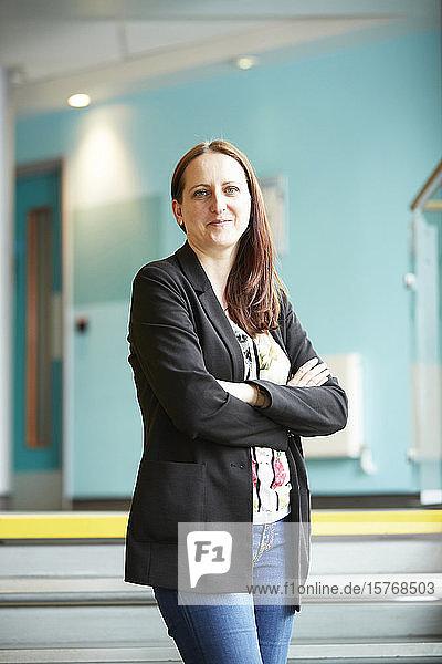 Portrait confident female teacher with arms crossed