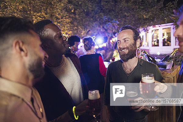 Glückliche männliche Freunde trinken Bier auf einer Gartenparty