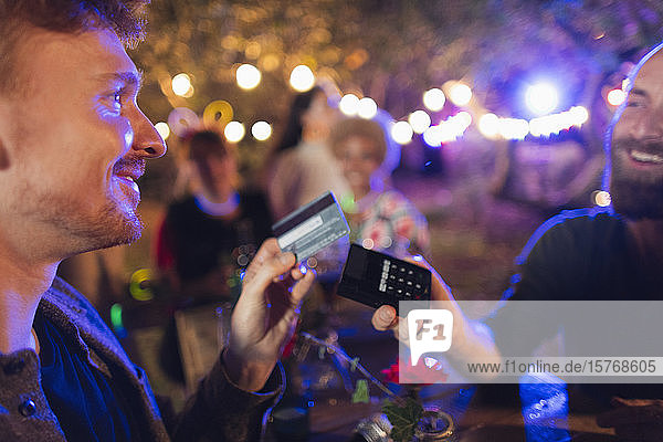 Man with credit card paying bartender at party Man with credit card paying bartender at party