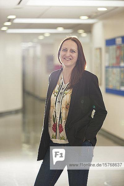 Portrait confident female teacher in corridor