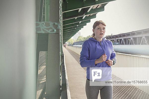 Dedicated young woman running along sunny train station platform