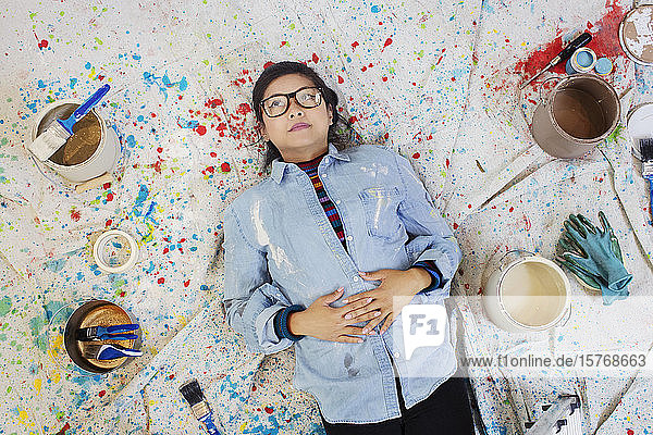 Woman taking a break from painting  laying on dropcloth among paint cans