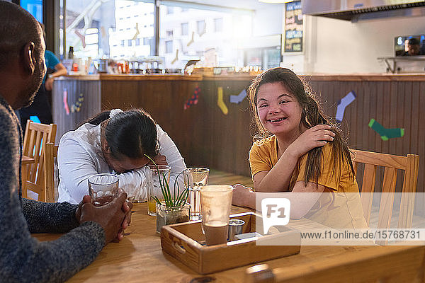 Happy young woman with Down Syndrome laughing with friends in cafe
