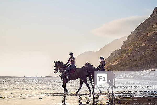 Young women horseback riding on tranquil ocean beach