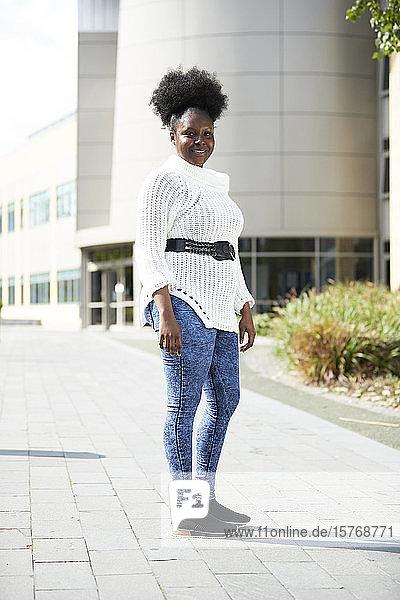 Portrait confident young woman outside sunny building
