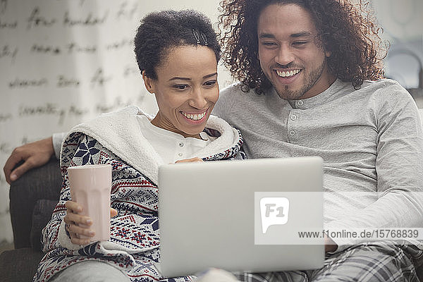 Happy couple in pajamas relaxing  using laptop on sofa